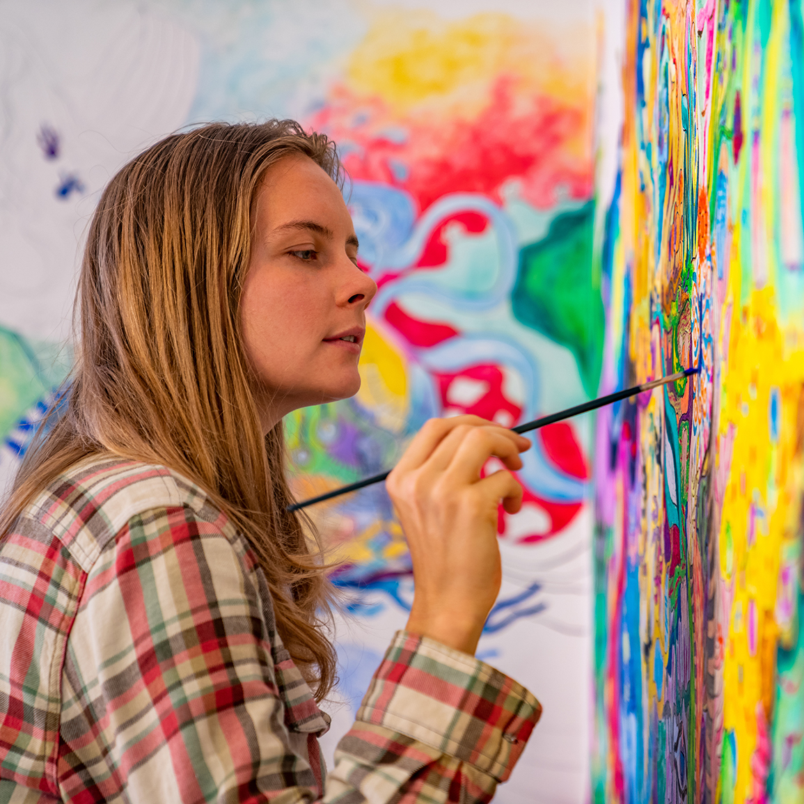 Joyful Young Female Artist Painting On The Wall, Using Brush And
